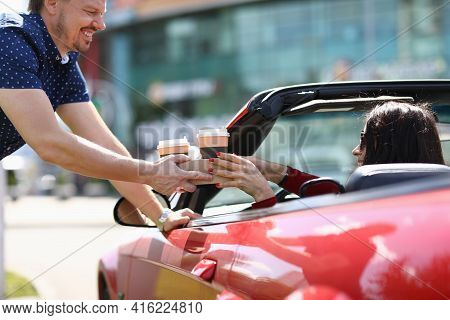 Man Serving Two Glasses Of Coffee To Woman In Red Convertible