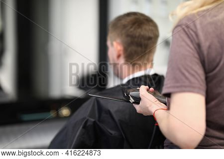 Hairdresser Doing Haircut To Young Man At Barbershop