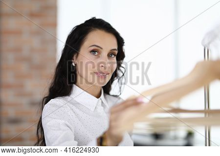 Young Woman Standing Near Rack With Hangers