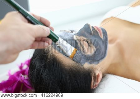 Beautician Applying Black Clay Mask To Woman With Brush