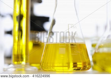 Test Tubes And Flasks With Yellow Liquid Standing On Table Of Chemical Laboratory Closeup