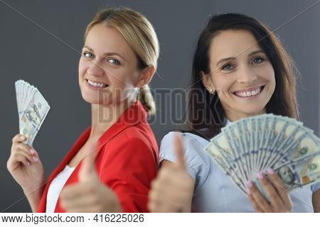 Two Young Women Are Holding Dollars And Showing Thumbs Up