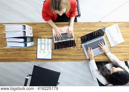 Female Colleagues Working On Laptop In Office Top View