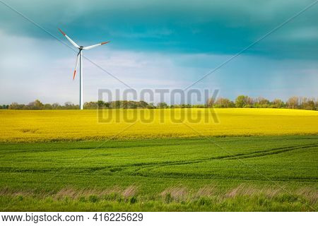 Green meadow and farmland with a wind turbine generating electricity