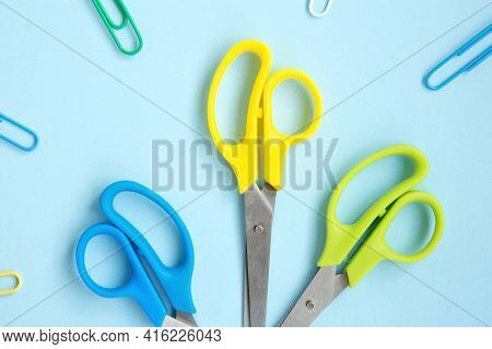 Set Of Blue, Yellow And Green Scissors On A Blue Background. School Stationery And Supplies. Back To