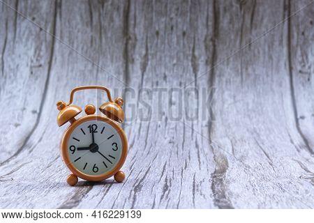Orange Old Retro Style Alarm Clock On Wooden Background. Alarm Clock Shows Nine O`clock