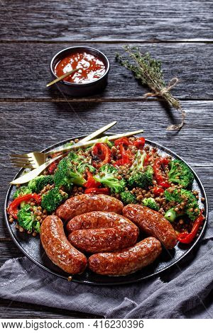 Italian Cotechino Pork Sausages Braised With Brown Lentils, Red Pepper, And Broccoli Served On A Bla