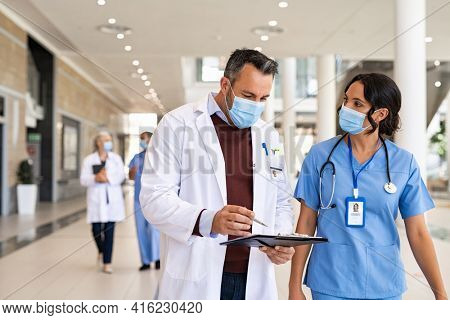General practitioner and nurse wearing surgical face mask against covid-19 while having a discussion in hospital hallway. Worried doctor showing medical report to nurse wearing protective face mask.