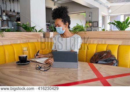 Black girl writing on agenda while using digital tablet sitting at cafeteria during coronavirus pandemic. University student studying at coffee shop and keeping social distancing and wearing face mask