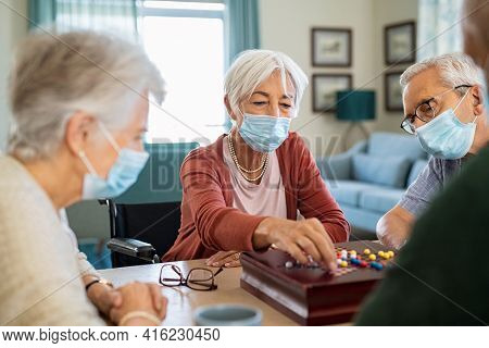 Senior woman wearing face mask and playing chinese checkers at home during covid-19 pandemic. Old woman with surgical face mask for safety against covid19 playing with friends at nursing home.
