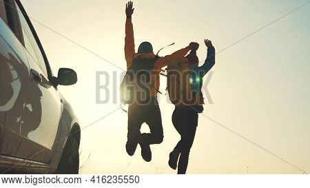 Business Teamwork A Success Concept. Couple Of Tourists With Backpacks Running Jumping Next Auto Sil