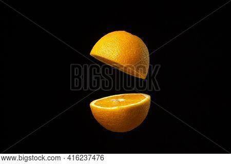 Orange Cut In Half In The Air Against A Dark Background. Sliced Orange On A Black Background. Creati