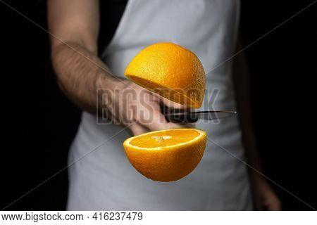 The Chef Cuts An Orange In The Air. A Knife Cuts An Orange On A Black Background. Creative Photograp