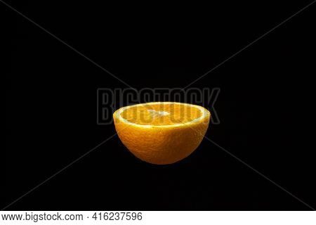 Half An Orange On A Dark Background. Sliced Orange On A Black Background. Creative Photography Of Or