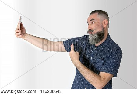 40-45 Year Old Caucasian Man With Big Gray Half Beard Putting Grimace And Victory Sign Towards His S