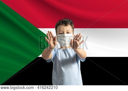 Little White Boy In A Protective Mask On The Background Of The Flag Of Sudan. Makes A Stop Sign With