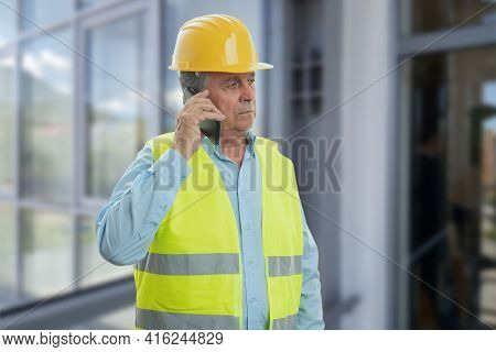 Old Male Builder With Serious Expression Wearing Fluorescent Work Vest And Yellow Hardhat Talking On