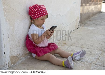 A Little Girl Sits On The Street And Looks At Her Mobile Phone, Leaning Her Back Against The Wall. C