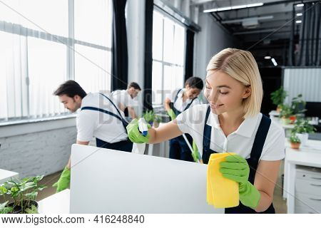 Cleaner Smiling While Cleaning Computer Monitor With Detergent In Office.