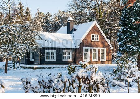 Snowy Wooden House In The Forest