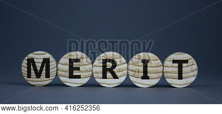 Merit Symbol. Wooden Circles With The Word 'merit'. Beautiful Grey Background, Copy Space. Business