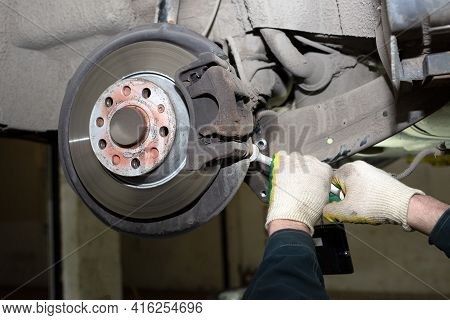 A Man Working In A Car Service. Replace Brake Disc And Pads. A Young Mechanic Is Repairing The Disc