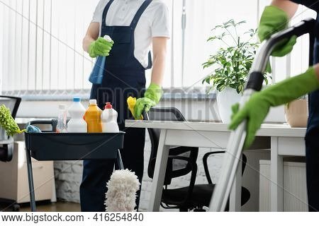 Cropped View Of Cleaner Holding Detergent Near Colleague With Vacuum Cleaner On Blurred Foreground I