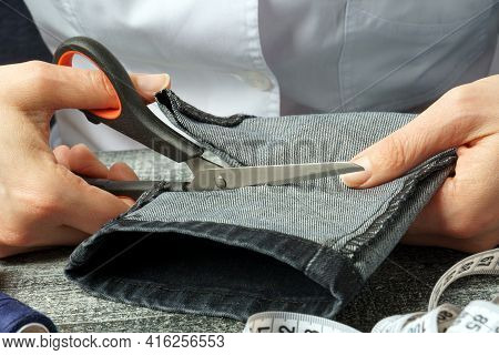 Seamstress Cuts Jeans Trousers With Scissors. Female Hands With Jeans And Scissors. Denim Pants Shor