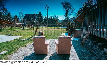 In The Spring, When The Snow Is Melting, A Young Woman Sits With Her Back To The Lens In A Chair Tha