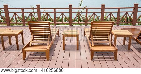 Row of chaise lounges with handrail in park by the sea