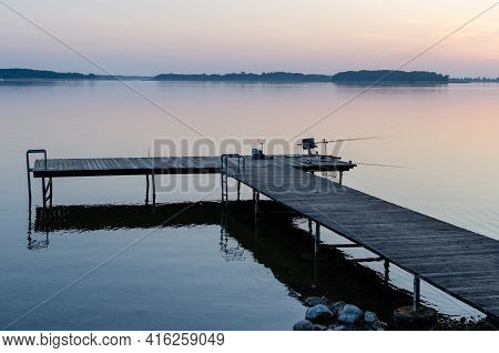 Fishing Equipment On The Pier At The Lake In Masuria. The Pier, The Quiet Święcajty Lake, Sunset
