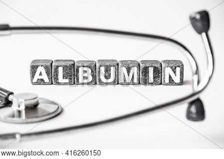 Stone Block Form Word Albumin With Stethoscope. White Background. Medical Concept. Protein Made By L