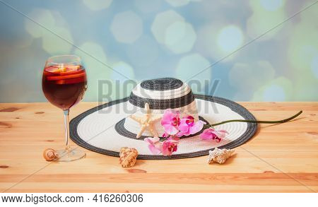White Summer Hat, Glass Of Red Wine Sangria, Purple Orchid, Starfish And Seashells On Blue Backgroun