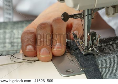 Process Of Shortening Jeans Pants On A Sewing Machine