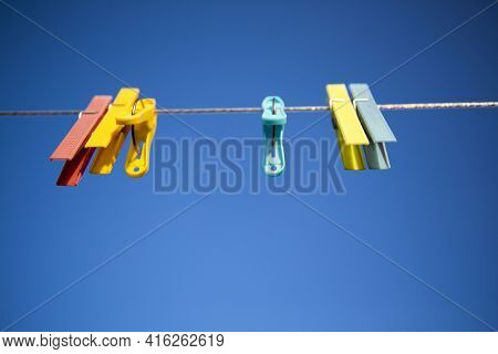 Clothes Line With Colored Clothespins Against A Blue Sky Background