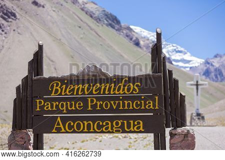 Welcome Wooden Sign At The Aconcagua National Park With The Peak Of The Mountain At 6962 Meters Abov