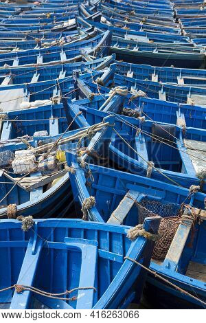 Group Of Blue Fishing Boats Aligned In The Harbour Of Essaouira, Morocco