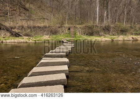 A River In The Woods With A Stepping Blocks Footbridge During Spring.