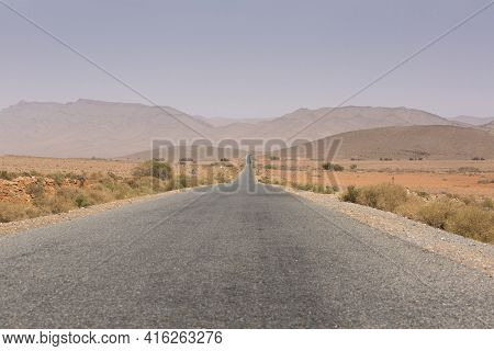 Straight Road Through The Desert In The Region Of Tata, Mountains In The Background. Morocco, Africa