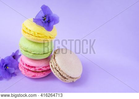 Colorful Macarons With Flowers One On Top Of Each Other On Purple Background.stack Of Delicious Colo