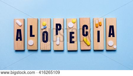 The Alopecia Is Written On Wooden Blocks On A Light Blue Table Near The Pills. Medical Concept