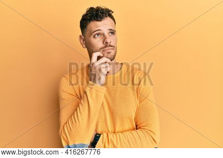 Young hispanic man wearing casual clothes thinking concentrated about doubt with finger on chin and looking up wondering