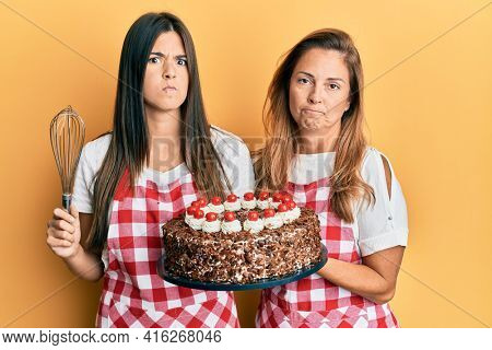 Hispanic family of mother and daughter wearing baker apron holding homemade cake skeptic and nervous, frowning upset because of problem. negative person.