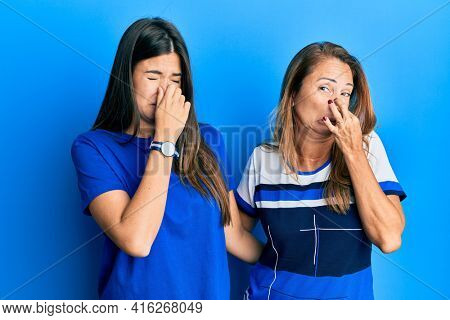 Hispanic family of mother and daughter wearing casual clothes over blue background smelling something stinky and disgusting, intolerable smell, holding breath with fingers on nose. bad smell