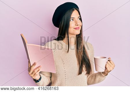 Young brunette woman reading a book and drinking a cup of coffee smiling looking to the side and staring away thinking.