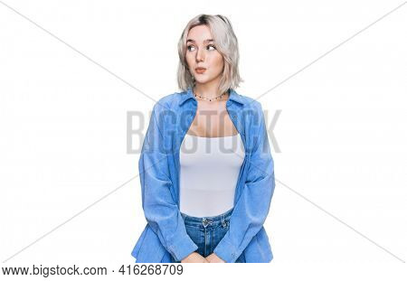 Young blonde girl wearing casual clothes smiling looking to the side and staring away thinking.