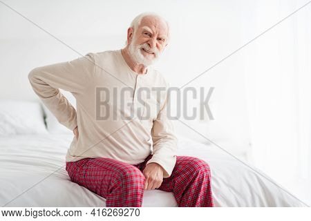 Photo Of Senior Man Unhappy Sad Upset Hand On Spine Ache Pain Spasm Disorder Sit On Bad Home Rest He