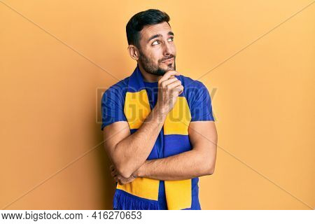 Young hispanic man football hooligan cheering game thinking concentrated about doubt with finger on chin and looking up wondering