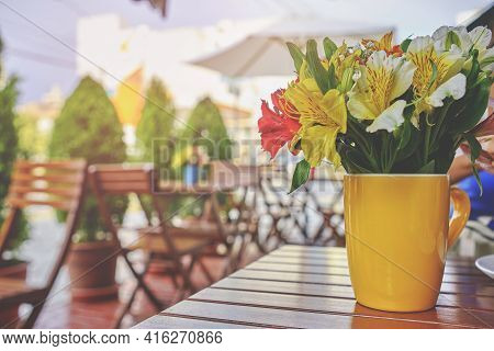 Romantic Coffee Shop, Cozy Street With Flowers And French-style Cafe Table. Empty Cafe Terrace With