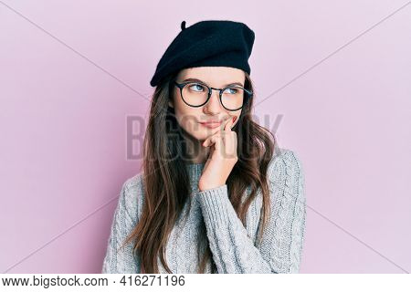 Young beautiful caucasian girl wearing french look with beret thinking concentrated about doubt with finger on chin and looking up wondering